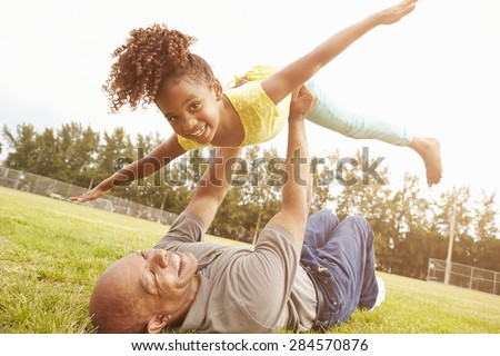 Grandfather Playing Game With Granddaughter In Park - stock photo