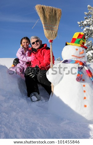 grandfather posing with granddaughter at ski resort - stock photo