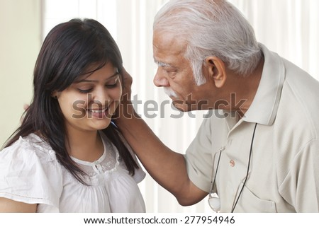 Grandfather pulling ears of granddaughter
