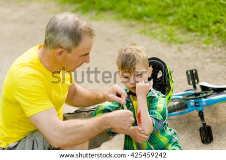 Grandfather putting band-aid on young boy's injury who fell off his bicycle