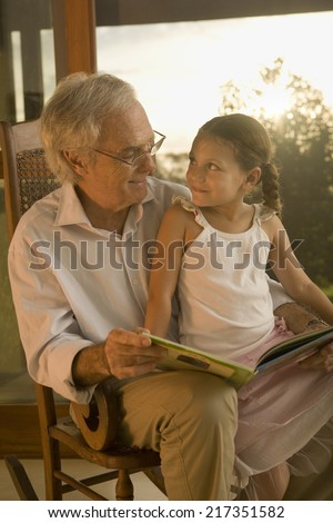 Grandfather reading to his granddaughter - stock photo