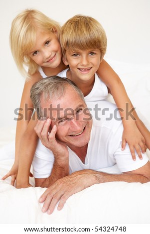 Grandfather Relaxing On Bed With Grandson - stock photo