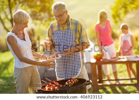 Grandfather serving food from barbecue grill for family