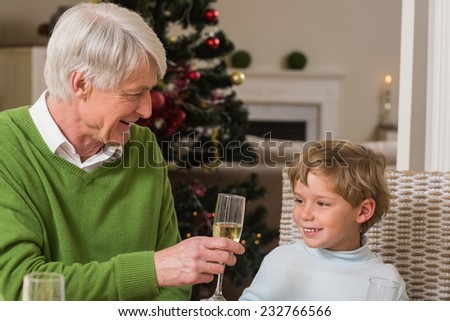 Grandfather showing glass of champagne to his grandson at home in the living room