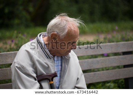 Grandfather sitting on a park bench thoughtfully