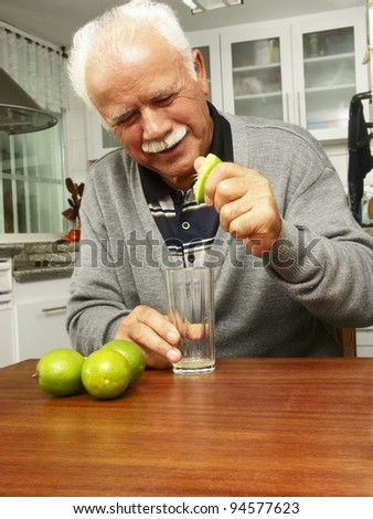 Grandfather squeezing a lemon in a kitchen. - stock photo