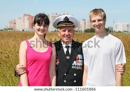 Grandfather stand in middle hug young couple near city - stock photo