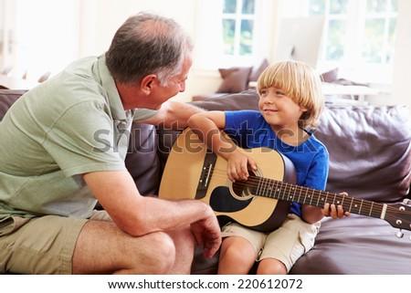 Grandfather Teaching Grandson To Play Guitar - stock photo