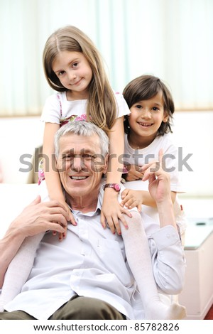 Grandfather with children, senior man at home with family - stock photo