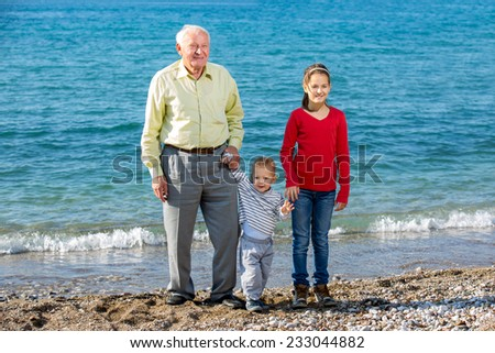 Grandfather with grandchildren standing by the sea - stock photo
