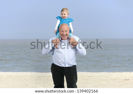 grandfather with granddaughter , outdoors at the beach - stock photo