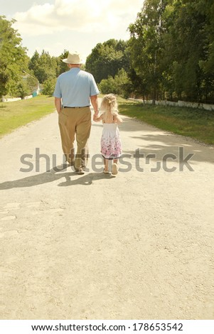 Grandfather with granddaughter walk along the road, - stock photo
