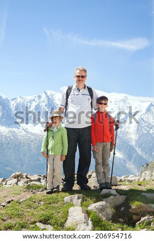 grandfather with her two grandchildren in a mountain hike - stock photo
