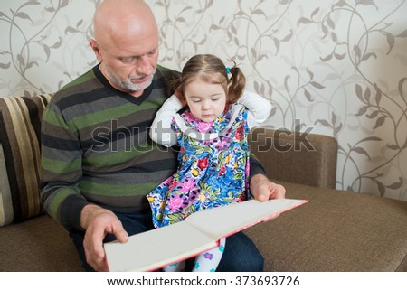 Grandfather with his little granddaughter reading a book
