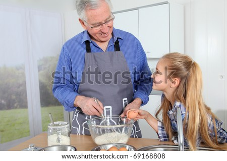 Grandfather with little girl preparing cake - stock photo