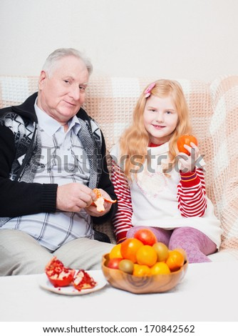 Grandfather with smile girl eating fruits at home - stock photo