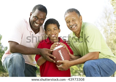 Grandfather With Son And Grandson In Park With American Football - stock photo