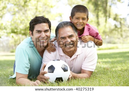 Grandfather With Son And Grandson In Park With Football - stock photo