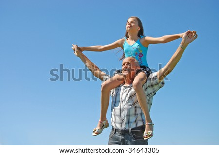 grandfather with the grand daughter against the dark blue sky - stock photo