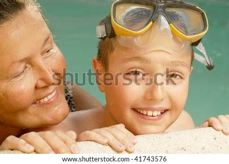 Grandma and her little guy exercising in the water together - stock photo