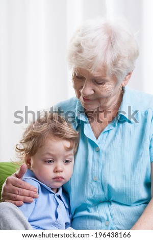 Grandma and sad little boy on couch - stock photo
