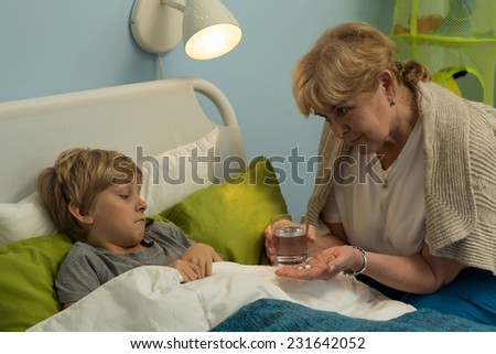 Grandma caring about his ill grandchild lying in bed - stock photo