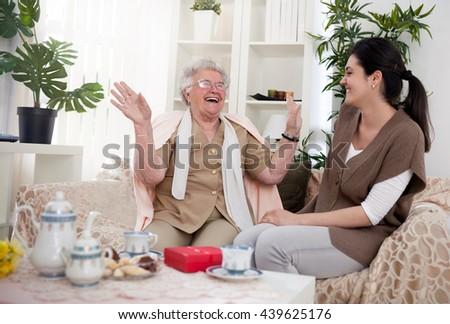 Grandma entertaining her granddaughter with fun stories - stock photo