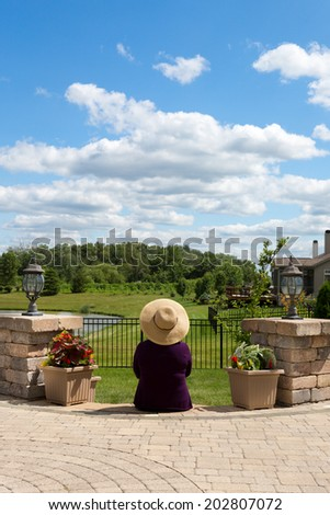 Grandma gardener taking a break to admire the view sitting with her back to the camera on the steps of her paved patio enjoying the scenic lush green countryside in the summer sun - stock photo