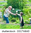 Grandma hands a dandelion seed to her grandson so he can blow on it. - stock photo