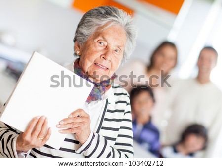 Grandma holding a book of cooking recipes - stock photo