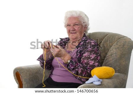 Grandma is sitting in a chair and knit some wool. Studio light white white background - stock photo