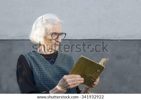 Grandma looking at family photo album in the backyard - stock photo