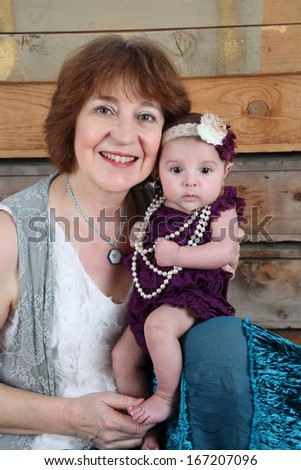 Grandmother and baby granddaughter against wooden background - stock photo