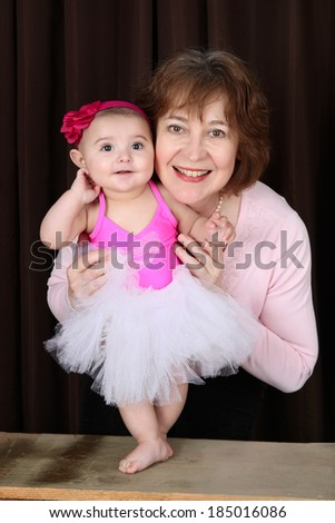 Grandmother and ballerina baby portrait against brown - stock photo