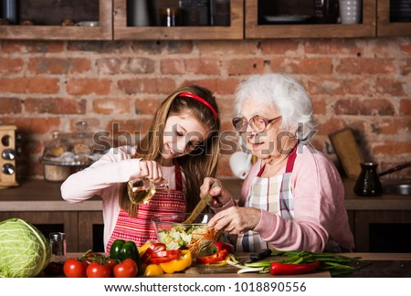 Grandmother and cute granddaughter cooking healthy food at home at kitchen