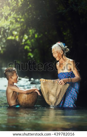 Grandmother and grandchildren are fishing in pond - stock photo