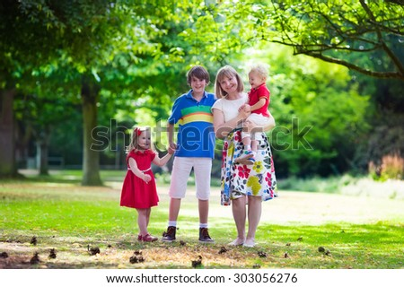 Grandmother and grandchildren enjoying picnic in a park. Grandma playing with children in a sunny autumn forest. Summer outdoor fun in the garden. Grandparents and kids on a meadow. - stock photo