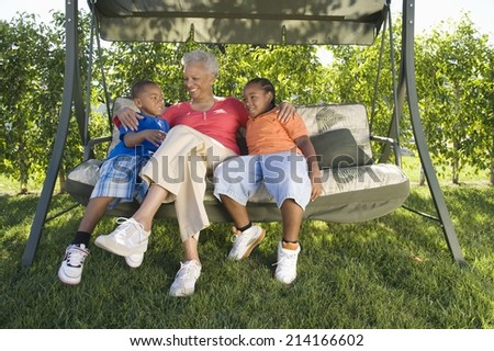 Grandmother and Grandchildren sitting on outdoor swing seat - stock photo