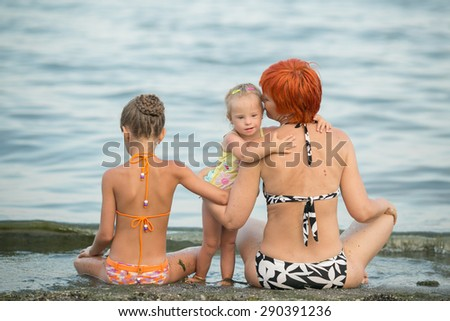 Grandmother and granddaughter doing yoga on the beach - stock photo