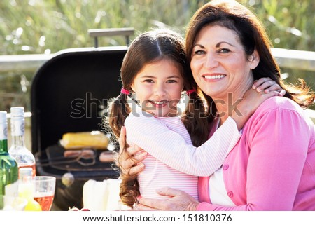 Grandmother And Granddaughter Having Outdoor Barbeque - stock photo