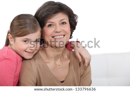 Grandmother and granddaughter hugging - stock photo
