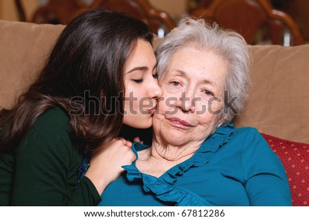 Grandmother and granddaughter in an affectionate lifestyle pose in a home setting. - stock photo