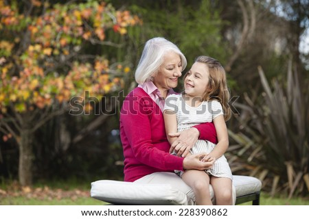 Grandmother and granddaughter in garden - stock photo