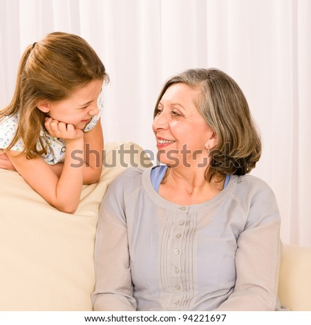 Grandmother and granddaughter look at each other relax on sofa