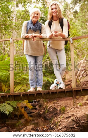 Grandmother and granddaughter on bridge in forest, vertical