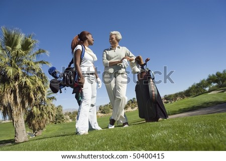 Grandmother and granddaughter on golf course, smiling - stock photo