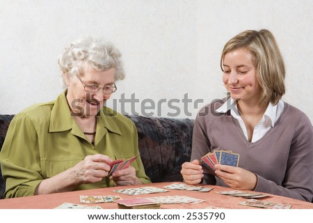 grandmother and granddaughter playing cards - stock photo