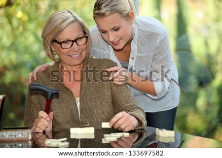 Grandmother and granddaughter playing dominoes - stock photo