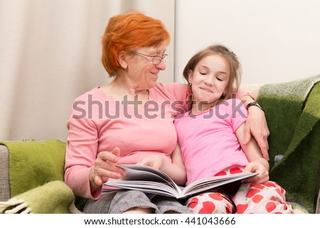 grandmother and granddaughter read book together and smile - stock photo
