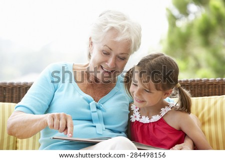 Grandmother And Granddaughter Reading Book On Garden Seat - stock photo